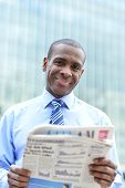 Handsome Male Executive Reading A Newspaper