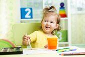 Kid Girl Painting On Paper In Nursery