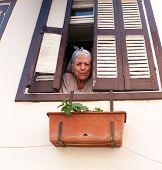 Elderly woman looks through window