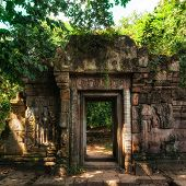 Entrance Gate Ruins Of Baphuon Temple With Growing Trees. Angkor Wat Complex, Siem Reap, Cambodia