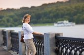 Beautiful Lady Enjoying The River View In The City Center At Sunset