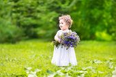 Beautiful Baby Girl With Curly Hair Carrying Flowers In A Garden