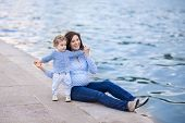 Portrait Of A Beautiful Young Pregnant Mother And Her One Year Old Baby Daughter At A River Bank