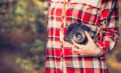 Young Woman with retro photo camera and plaid shirt outdoor