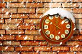 Snow-covered Clock On Background Of Old Brick Wall