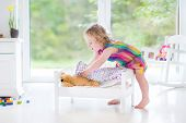 Cute Curly Toddler Girl Playing With Her Teddy Bear In A Sunny Bedroom With Big Windows
