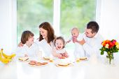 Happy Young Family fun together during an Easter breakfast in a white sunny dining room