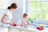Young Beautiful Mother And Her Cury Curly Toddler Daughter Washing Vegetables Together In A Kitchen