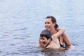 Mother And Son Swimming In Lake