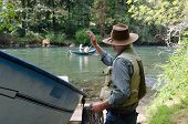 pic of mckenzie  - A man waves to other fishermen in a Mckenzie River drift boat. The flat bottomed design without a keel was developed for navigating this popular Oregon near Eugene.