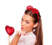 Beautiful brunette with heart shape glasses holding heart and sending kisses, on white background