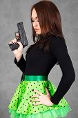 Portrait Of A Young Attractive Woman In A Bright Green Skirt With A Gun