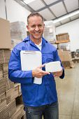 Smiling warehouse worker holding small box and clipboard in a large warehouse