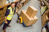 image of trolley  - Worker with trolley of boxes smiling at camera in a large warehouse - JPG