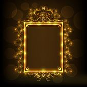 Beautiful floral design decorated frame in shiny golden color on brown background.