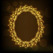 Shiny golden floral design decorated frame on brown background.