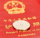 pic of yuan  - Chinese one yuan coin against the background of the Chinese passport - JPG
