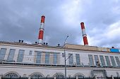 stock photo of chp  - High chimneys over the building of CHP on cloudy sky background - JPG