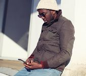 Lifestyle Portrait Of Stylish Young African Man Using Smartphone In City - Street Fashion And Techno