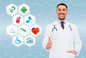 healthcare, profession, symbols, people and medicine concept - smiling male doctor with stethoscope in white coat over blue background with medical icons