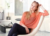 Attractive nordic type woman sitting at home in chair, daydreaming.
