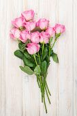 Pink roses bouquet over white wooden table. Top view