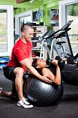 stock photo of personal trainer  - A shot of a male personal trainer assisting a woman lifting weights - JPG