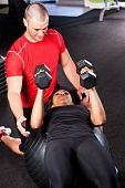 picture of personal assistant  - A shot of a male personal trainer assisting a woman lifting weights - JPG