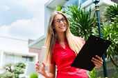 Female Architect with folding rule and clipboard in front of house