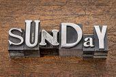 Sunday word in mixed vintage metal type printing blocks over grunge wood
