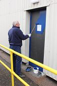 stock photo of roller door  - A painter painting a door using a gloss roller - JPG