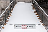 pic of stairway  - Sign of closed stairway in french and English with a stairway in background full of snow - JPG
