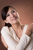 Asian young woman with happiness expression, closeup portrait on studio brown background.