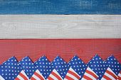 High angle shot of American Flag napkins spread out on a red, white and blue picnic table. Horizontal format with copy space. Suitable for American Holidays: 4th of July and Memorial Day,