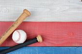 High angle shot of a baseball and bats on a red, white and blue picnic table. Horizontal format with copy space. Suitable for American Holidays: 4th of July and Memorial Day,
