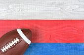 High angle shot of an American style football on a red, white and blue picnic table. Horizontal format with copy space. Suitable for American Holiday: 4th of July and Memorial Day,