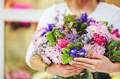 Female florist holding big bouquet of various flowers