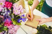 Hands of female florist with pencil making notes