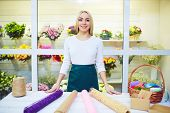 Happy young woman looking at camera at the counter of flower shop
