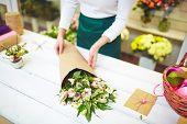 Female florist selling bouquet of amaryllises