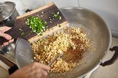 Adding scallion into the fried rice while stirring it with spatula, movement blur noticeable