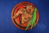 meat food : roasted chicken legs garnished with green onion pens and peppers on wooden plate over blue wooden background