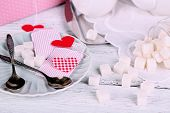 Heart shaped teabag tags, spoon and sugar cubes on saucer on wooden background