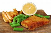 Breaded fried fish fillet and potatoes with asparagus and sliced lemon on wooden cutting board isolated on white