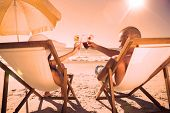 Happy couple on the beach clinking their glasses while relaxing on their deck chairs
