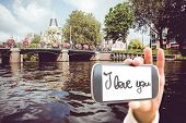 Hand holding smartphone showing against canal in amsterdam