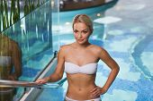 people, beauty, spa, healthy lifestyle and relaxation concept - beautiful young woman in bikini swimsuit raising upstairs in swimming pool
