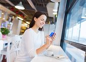 drinks, food, people, technology and lifestyle concept - smiling young woman with smartphone drinking coffee at cafe