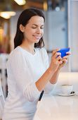 leisure, drinks, people, technology and lifestyle concept - smiling young woman with smartphone drinking coffee at cafe