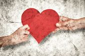 Hands holding red heart against grey background